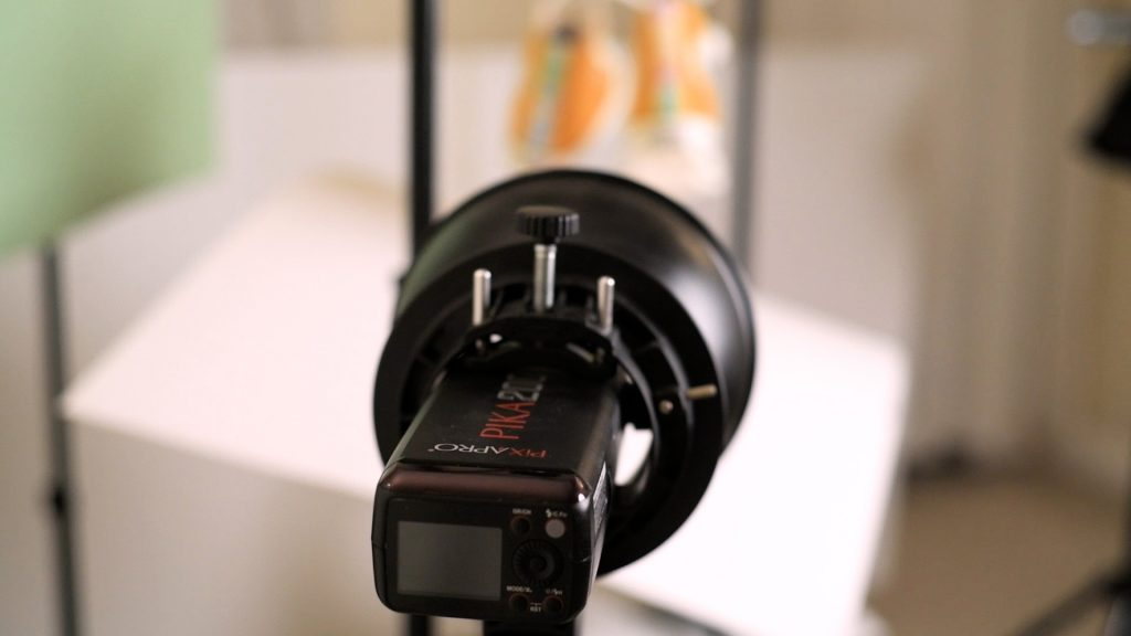 A Pika200 with standard 55 degree reflector is aimed at the base of the product being photographed.
